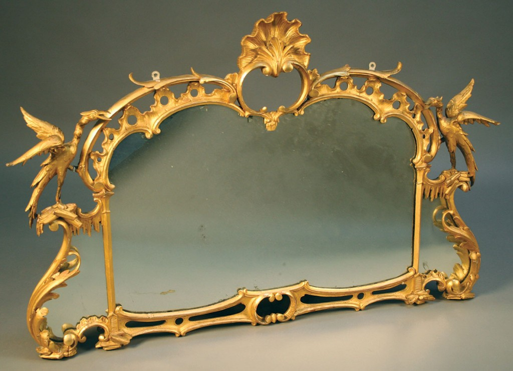 A George III Rococo gilt-framed wall mirror with shell surmount and fabulous birds.