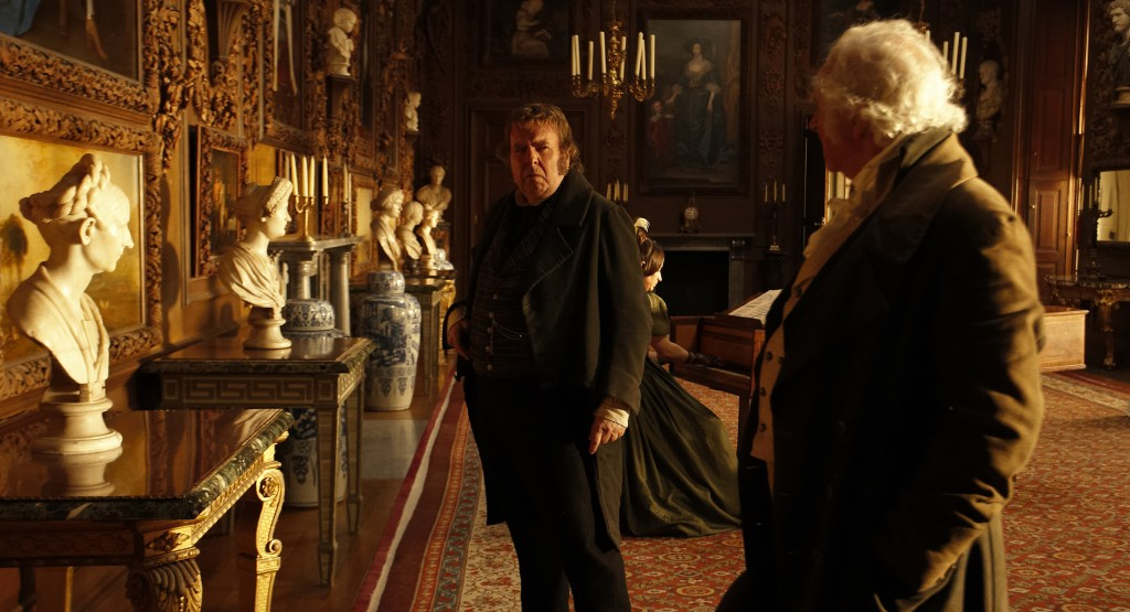A scene from Mr. Turner in the Carved Room at Petworth House, with Timothy Spall, Karina Fernandez and Patrick Godfrey playing J.M.W. Turner, Mrs Coggins and the 3rd Earl of Egremont © Thin Man Films