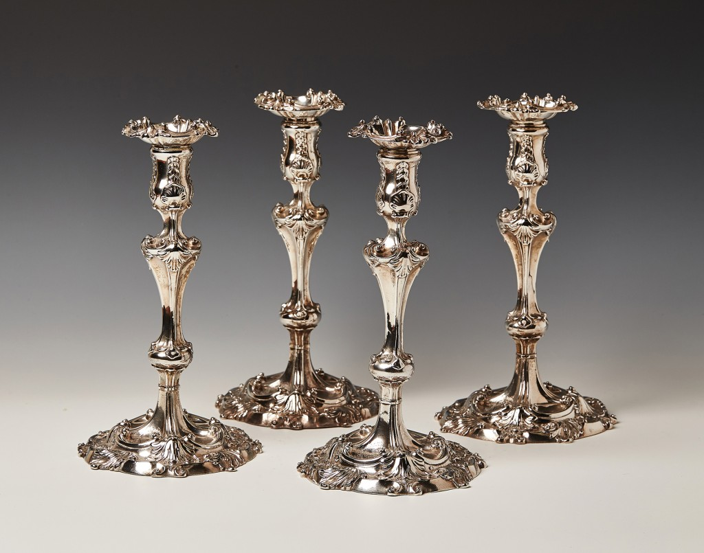 A set of four George II cast silver Rococo candlesticks by Alexander Johnston