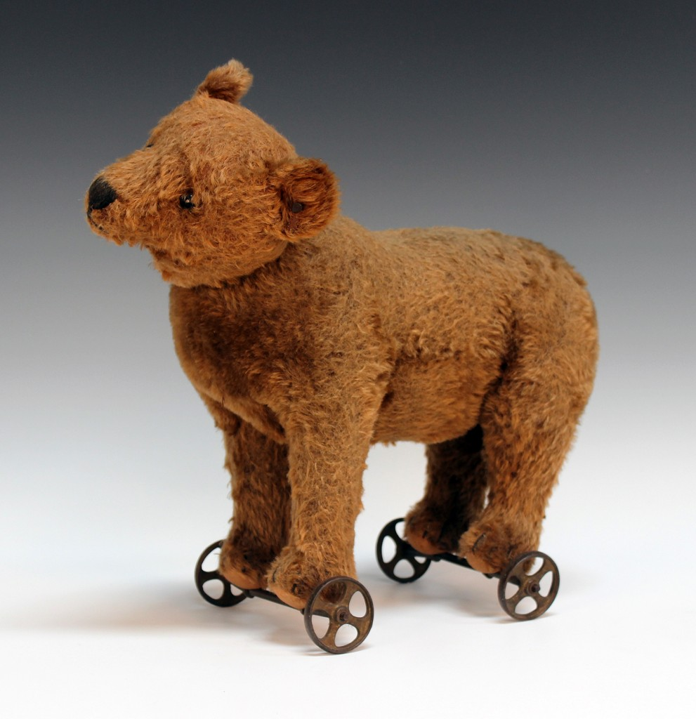 A Steiff mohair bear on wheels, with gilt button and tab in left ear, on cast metal axles and spoked wheels