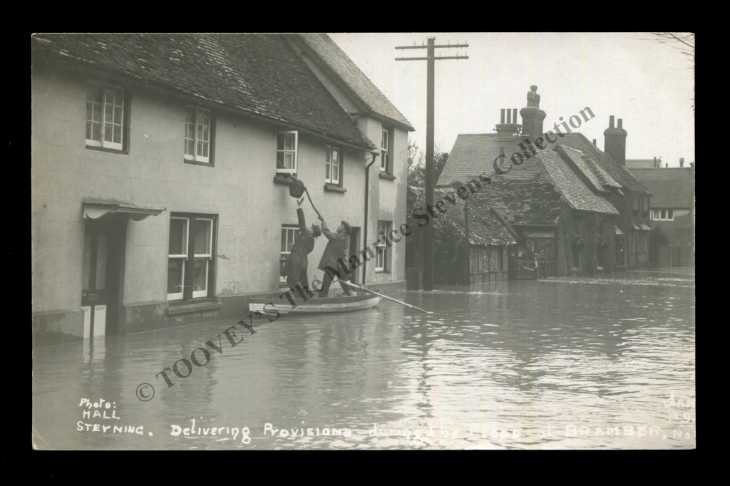 A photographic postcard 'Delivering Provisions during the flood at Bramber', circa 1924