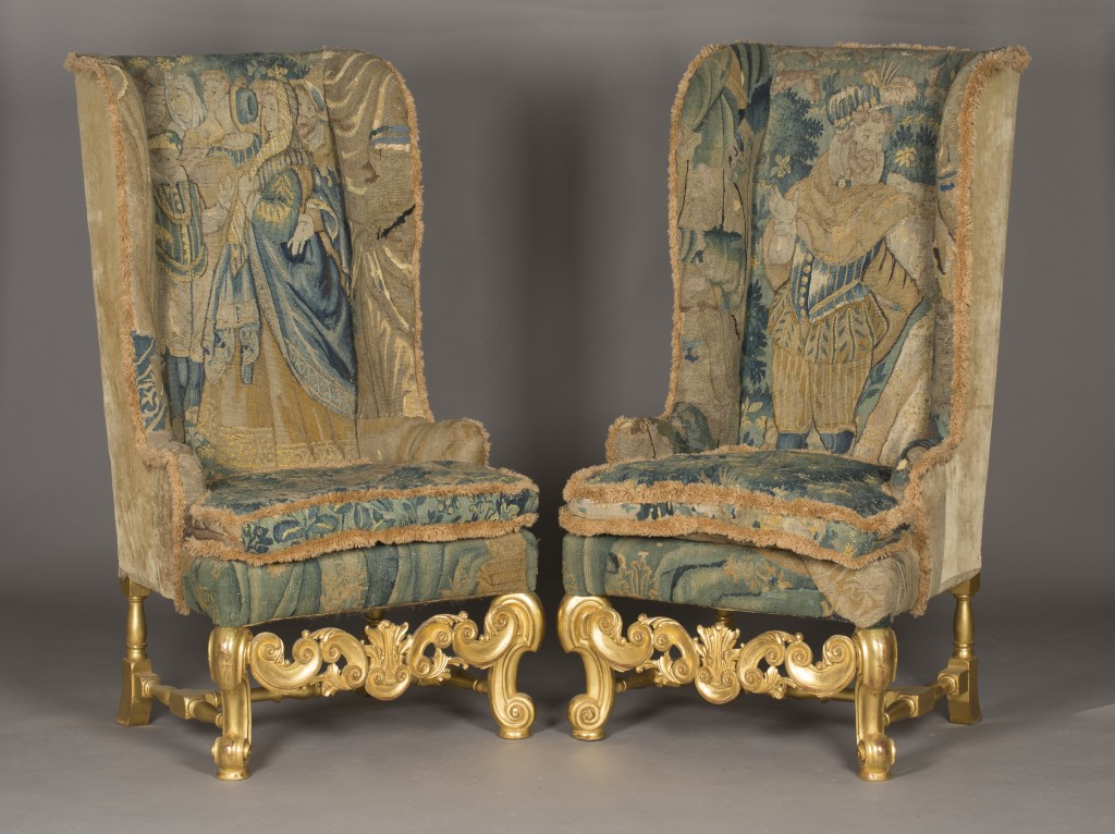 A pair of late wing back armchairs in the 17th century taste, upholstered in overall verdure tapestry panels