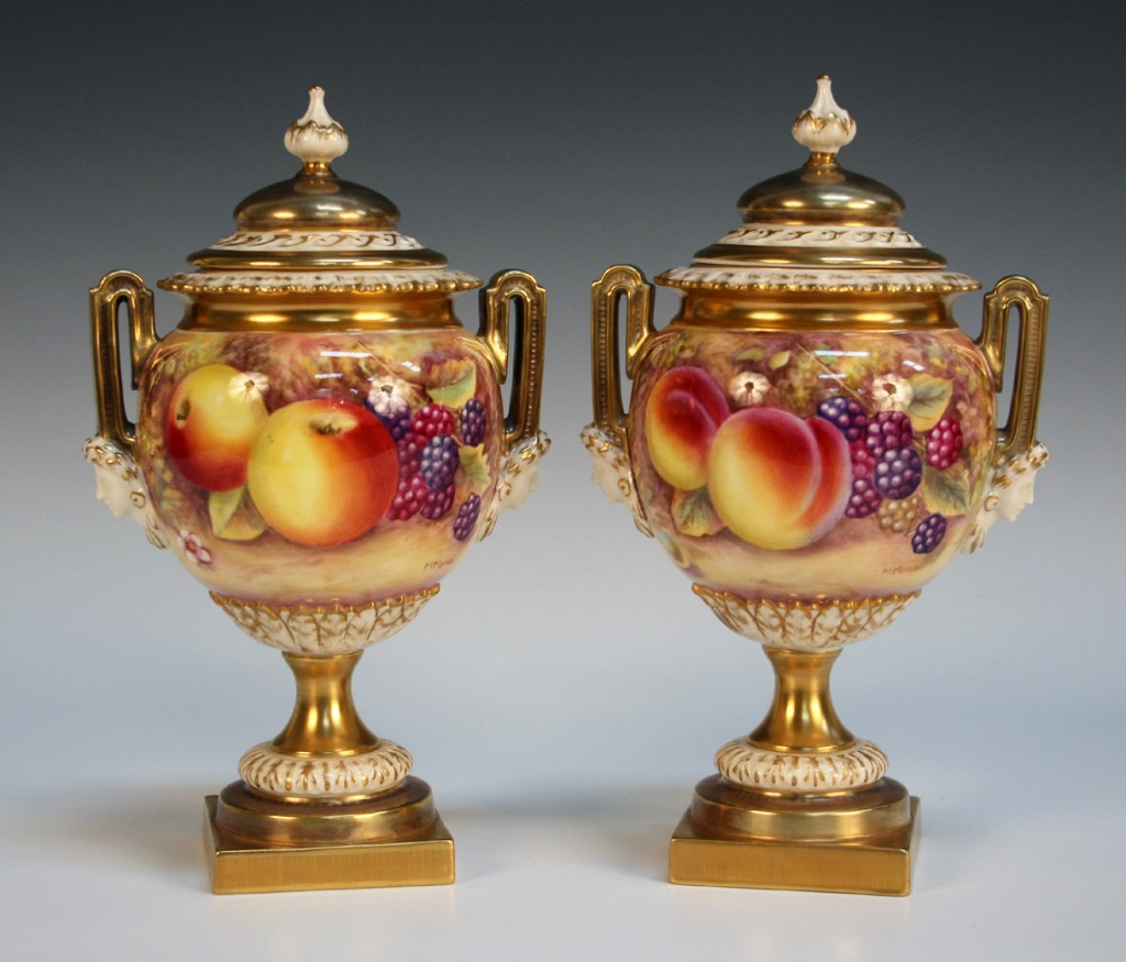 A pair of Royal Worcester bone china two handled urns and covers, painted by M. Morris, after 1950 with still life studies of fruit