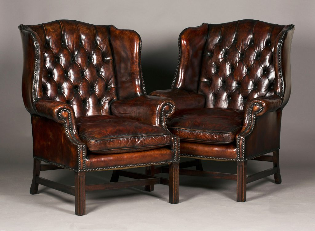 A pair of 20th Century George III style buttoned brown leather wing back armchairs sold for a hammer price of £1400