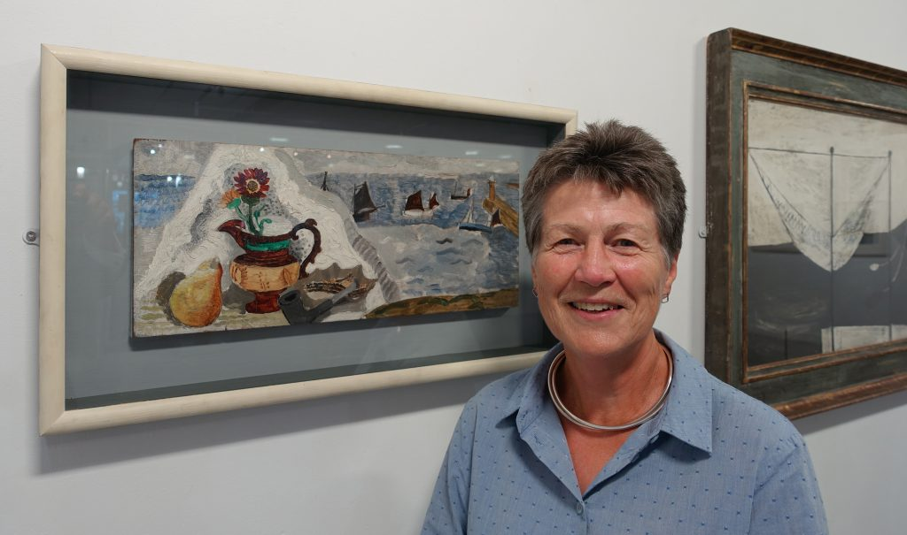 Visiting Professor and Guest Curator Gill Clarke in the Otter Gallery with Christopher Wood's oil on panel, Still Life with Boats, c.1930