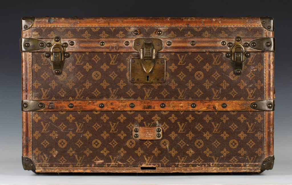 A Louis Vuitton travelling trunk with overall LV monogram decoration on a brown ground and a paper label inscribed '1 Rue Scribe, Paris, Louis Vuitton, 149 New Bond St. London' and numbered '108407'