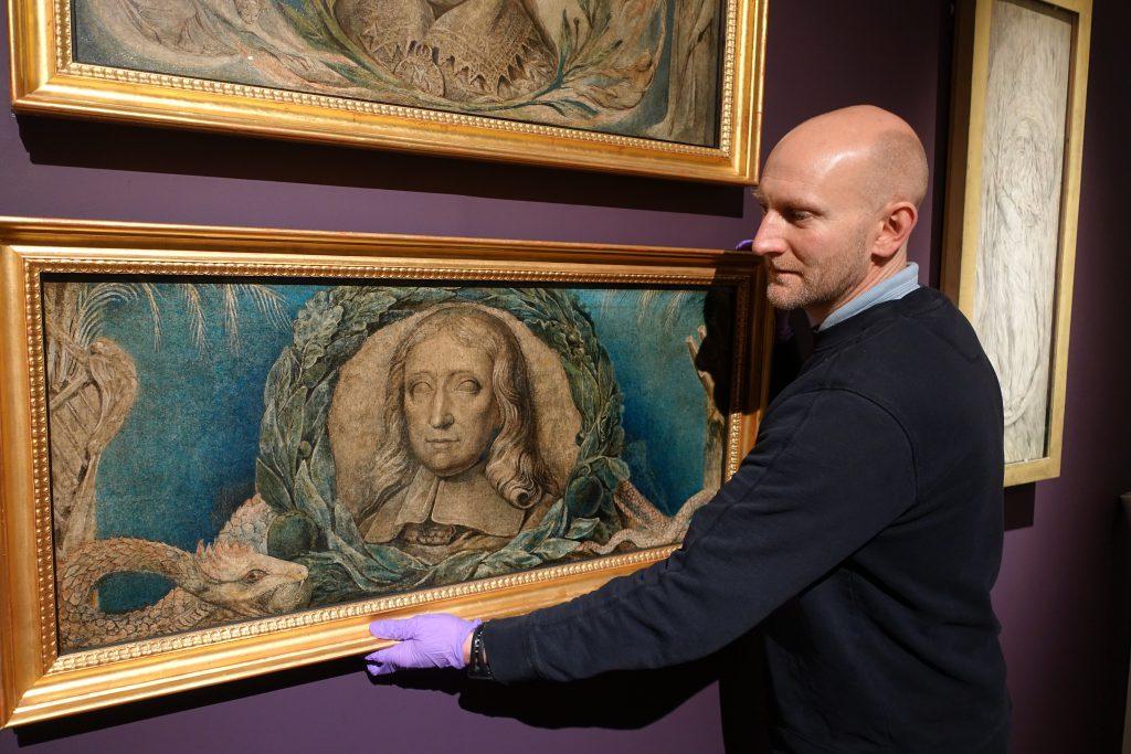 Exhibition curator Andrew Loukes with William Blake's 'John Milton', c. 1800-03