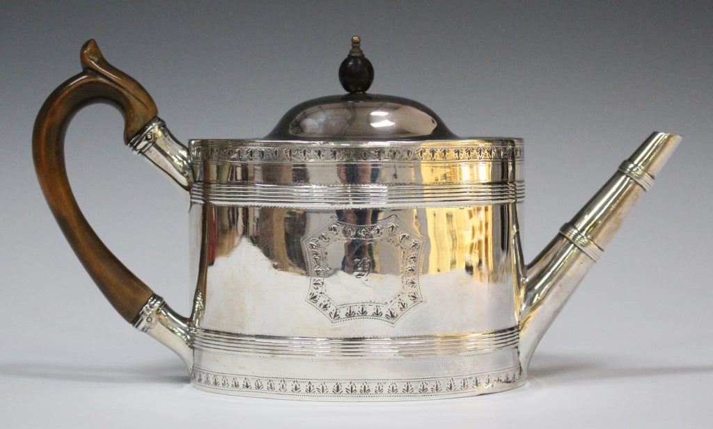 A George III silver teapot of oval form, engraved on each side with a floral garland cartouche within a banded and floral garland border, London 1791 by Robert Hennell I