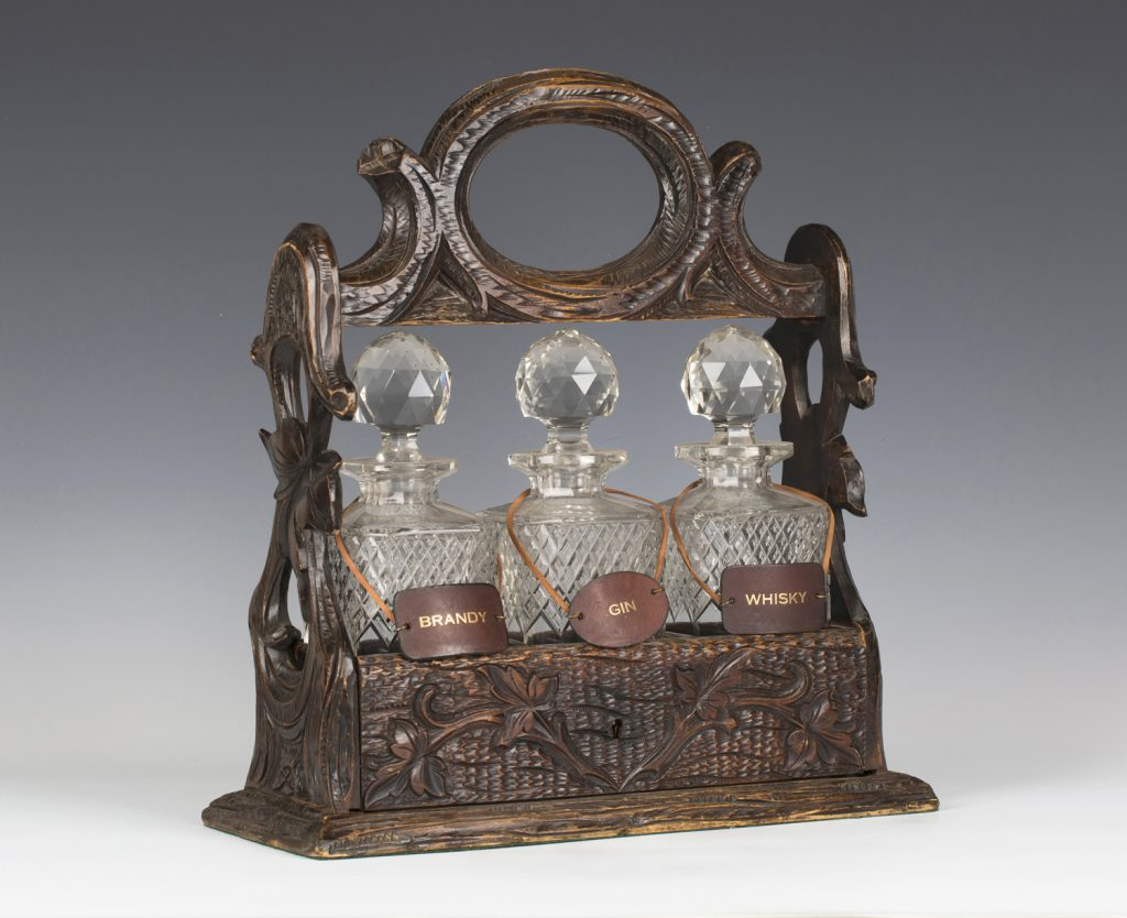 A late 19th century Black Forest carved softwood three bottle tantalus from the Lenson-Smith Collection
