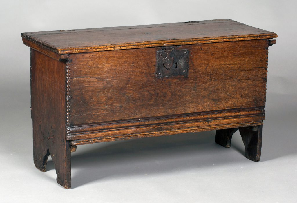 A mid-17th century oak six plank coffer, the edges with chip carving and the lid retaining its original wire hinges