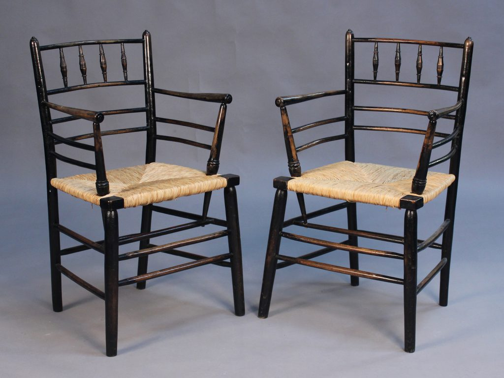 A pair of late 19th Century ebonized Ash Sussex armchairs by Morris & Co, with turned spindle backs above rush seats, on turned legs