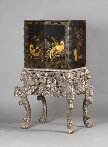 An early/mid-18th century Japanese lacquer cabinet with an English silvered, carved wood and gesso Baroque stand